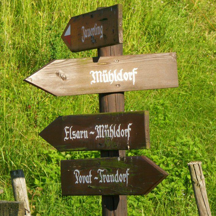 Holzschild Mühldorf mit grüner Wiese im Hintergrund