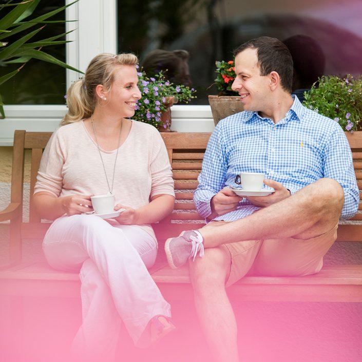 Birgit und Roman Siebenhandl sitzen auf einer Bank vor dem Gasthof