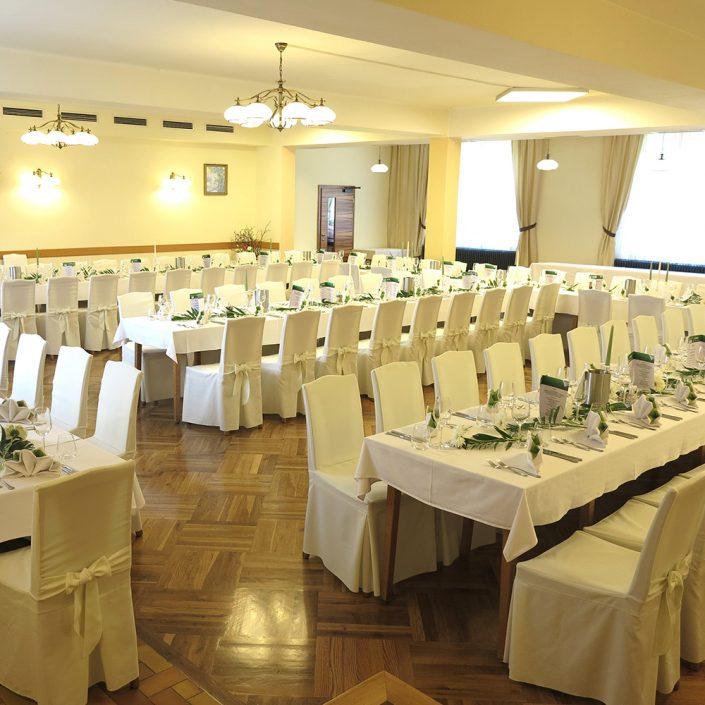 grosser Speisesaal mit gedeckten Tischen für eine Feier