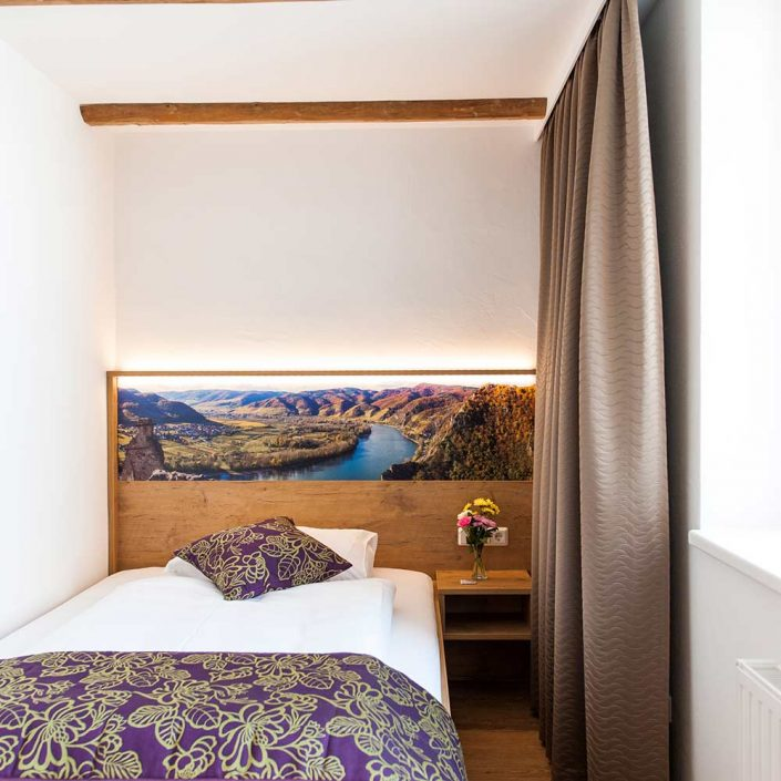 Einzelbett mit Nachtkästchen und Bild der Donau