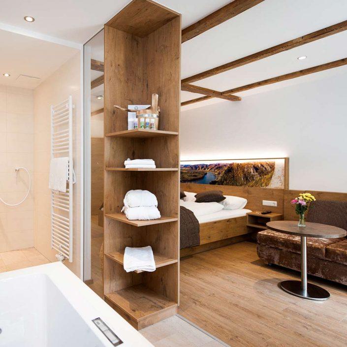 Blick vom Badezimmer auf das Doppelbett und die Couch